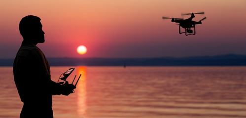 Man flying a drone near seaside at the sunset