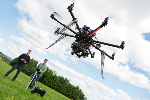 Technicians Operating UAV Helicopter in Park