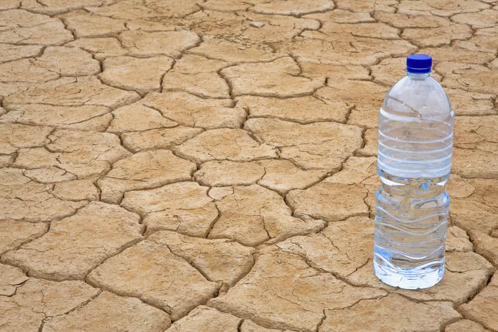 Hard Water in a bottle on dry ground