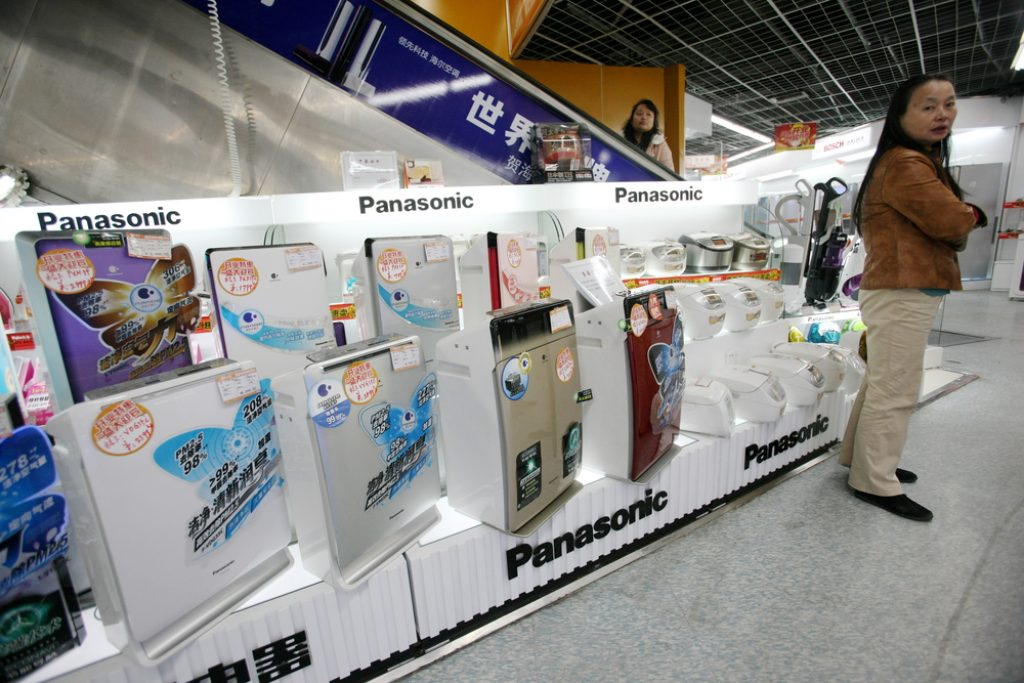 A Chinese customer stands next to air purifiers