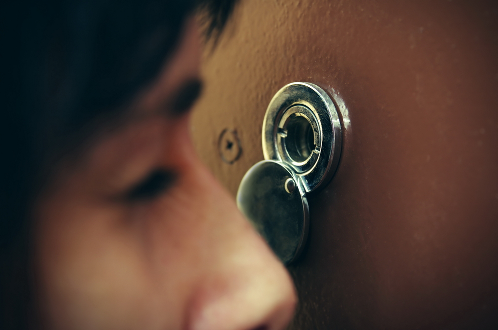Closeup of woman looking through peephole