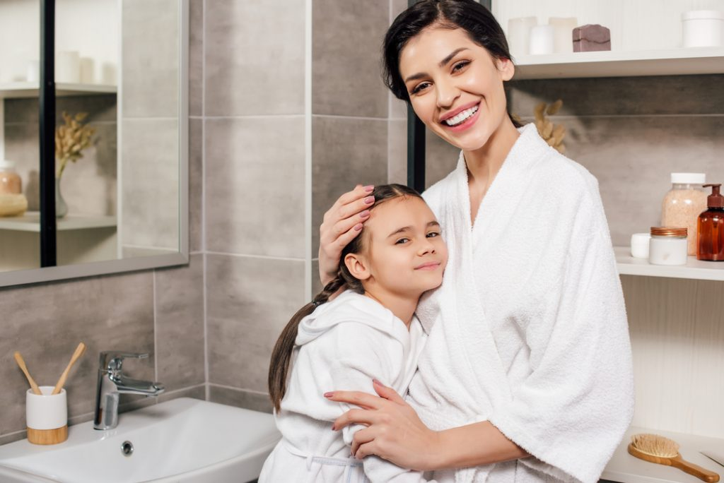 Daughter And Mother In White Bathrobes Hugging In Bathroom