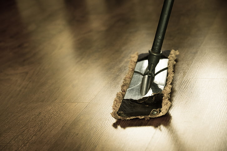 A Gray Mop On A Brown Laminated Floor