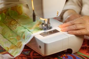an experienced woman who sews using her sewing machine