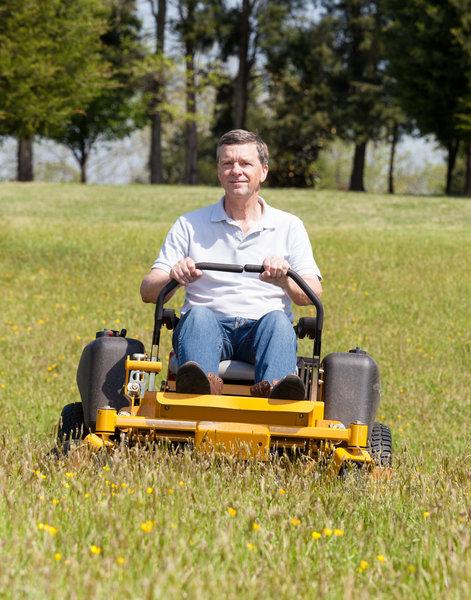 Senior man on zero turn lawn mower on turf