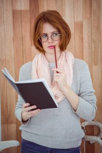 pensive hipster woman with a notepad and pencil