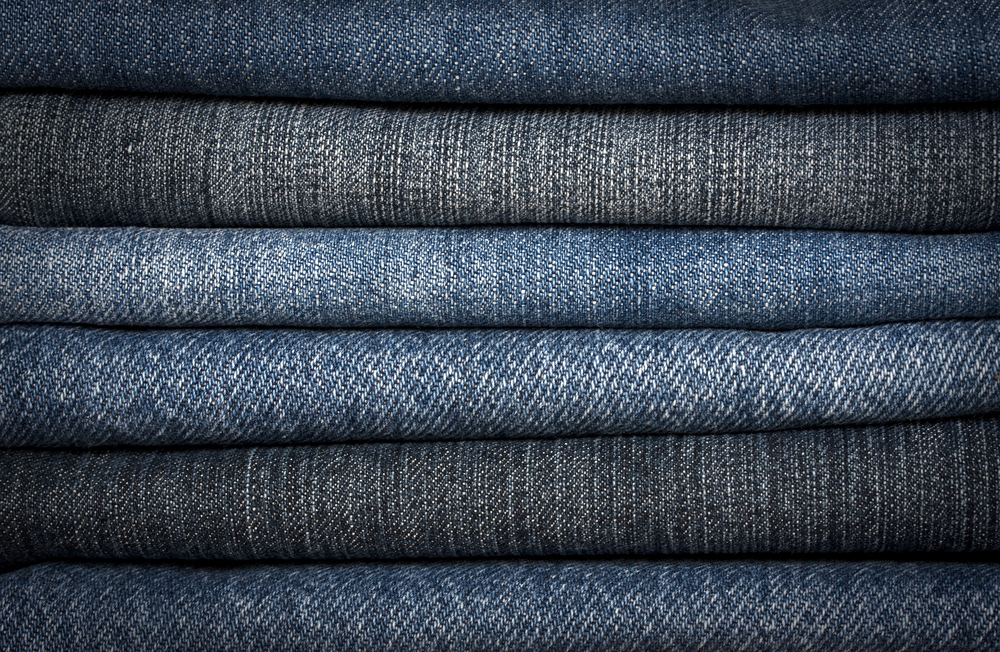 A pile of different types of blue denim jeans